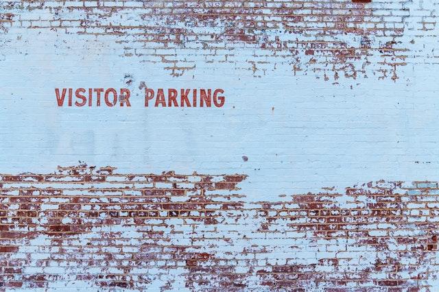 """Nápis na stene """"visitors parking"""""""