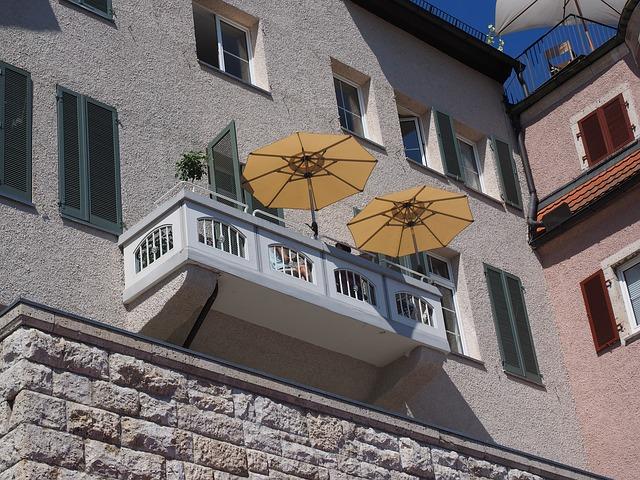 Balkón so zábradlím a dvoma oranžovými slnečníkmi.jpg