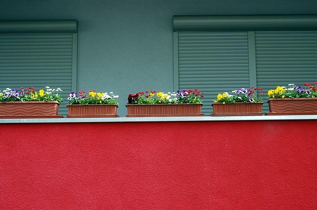 Balkón s červeným zábradlím a kvetináčmi s kvetmi.jpg