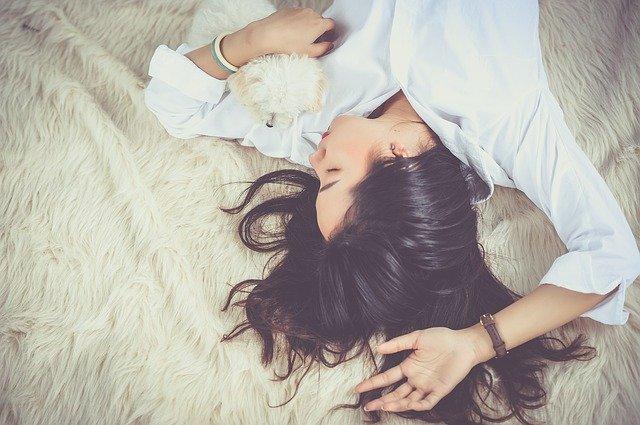 Žena v bielej košeli leží na posteli s malým bielym psom.jpg
