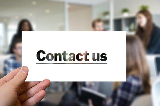 "Človek drží v ruke lístoček s nápisom ""kontaktujte nás"""